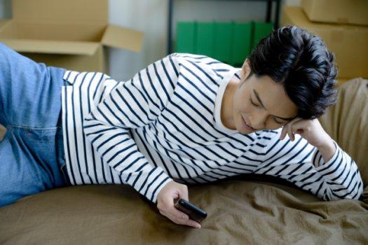 寝転んでスマホをいじる男性