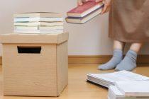 本を整理する女性の足元