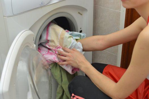 ドラム式洗濯機から洗濯物を取り出す女性